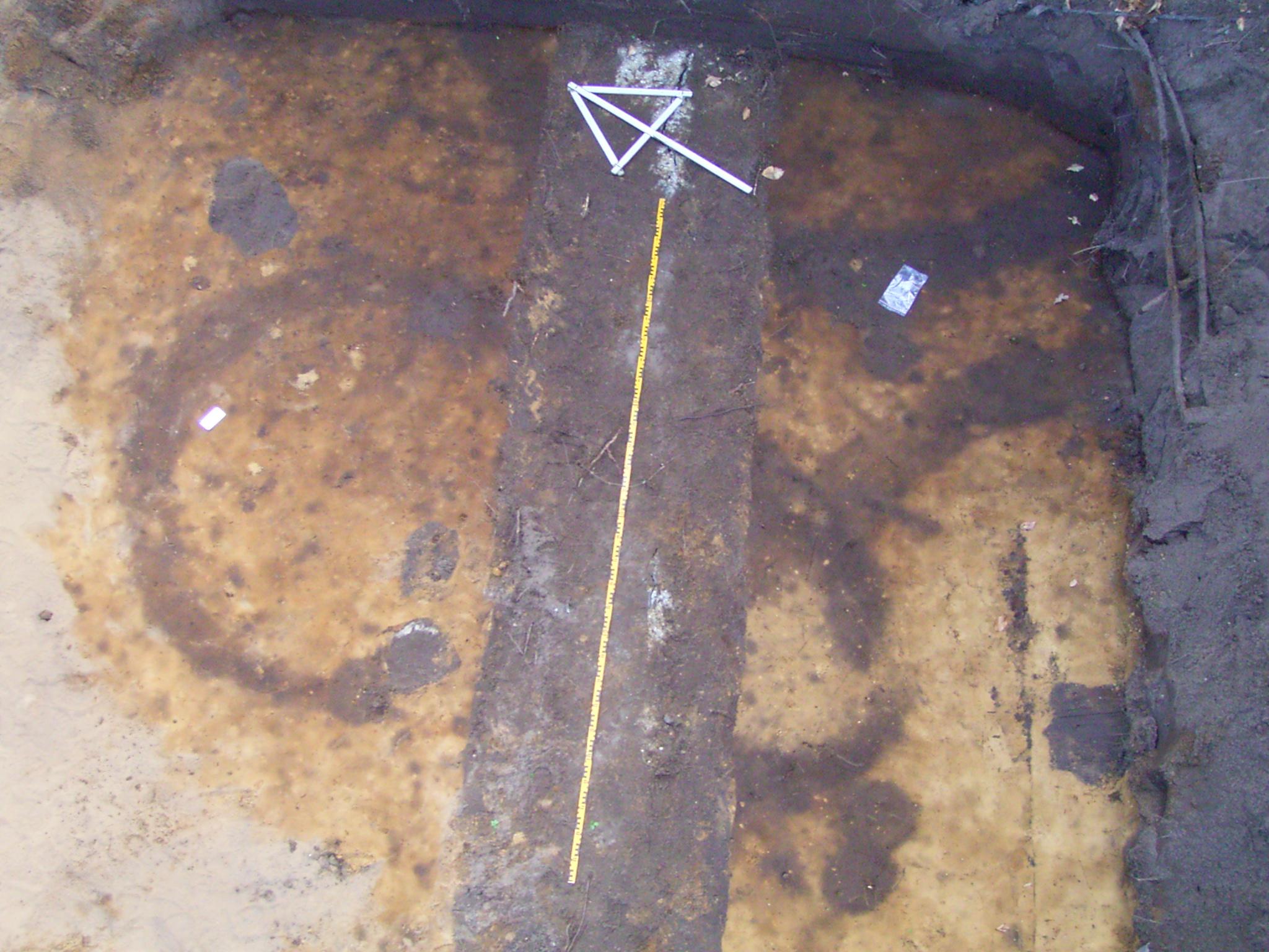 Opgraving Doornseweg - Kringgreppels van begravingen uit circa 1000 c. Chr. De brede verkleuring waard e meetlat op ligt is een recente verstoring