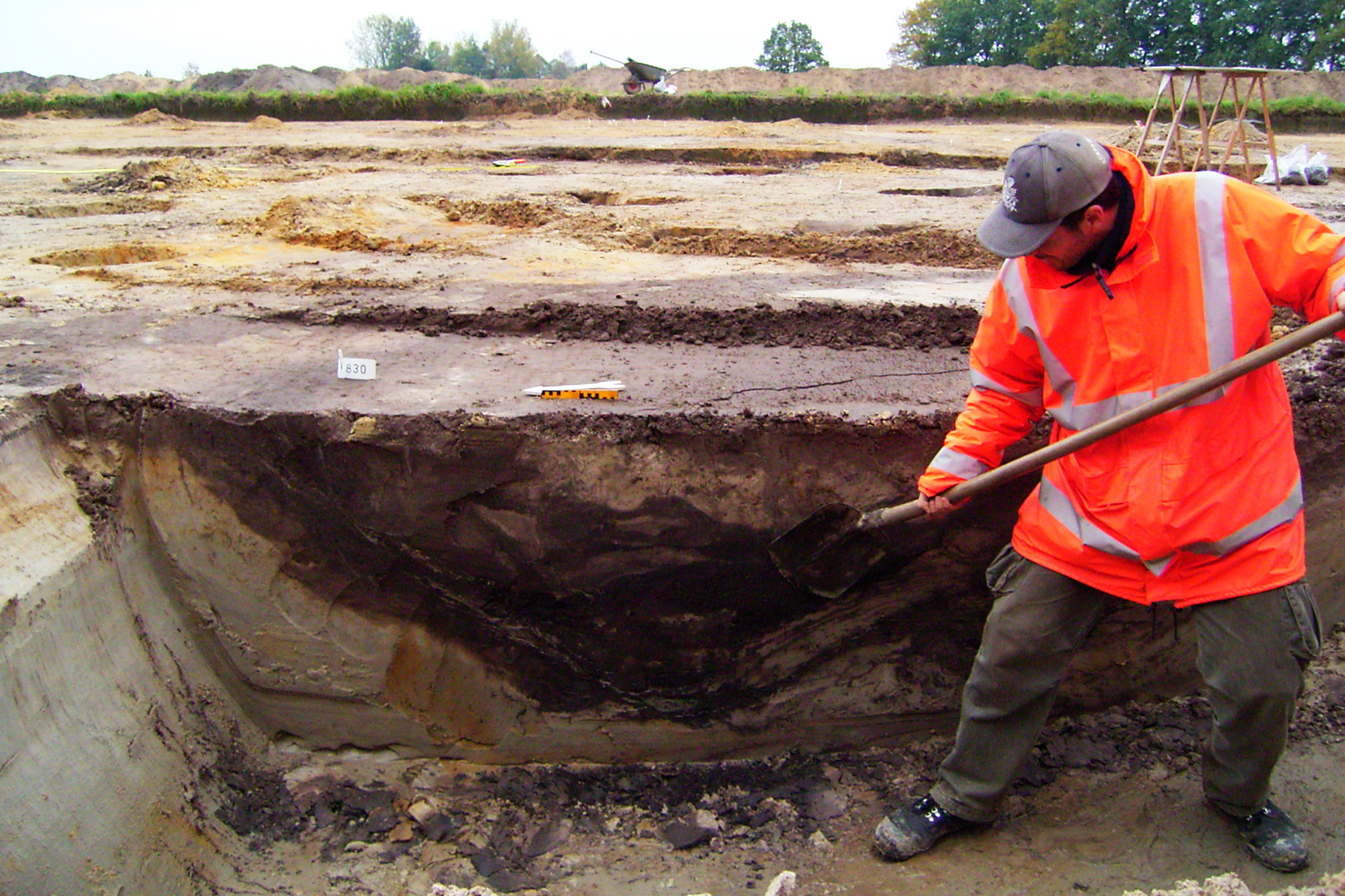 Opgraving Schammer - Archeoloog schaaft het profiel van een grote kuil